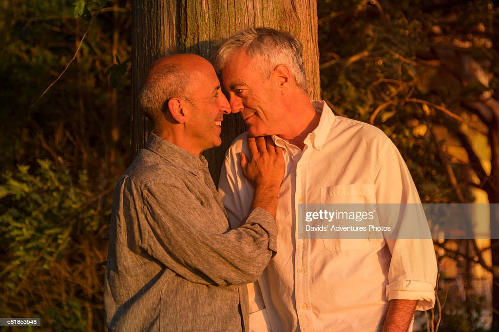 Senior Gay Couple Affectionately Holding Each Other At