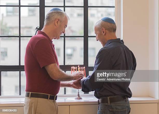 senior gay couple affectionately lighting chanukah menorah - gay seniors photos et images de collection