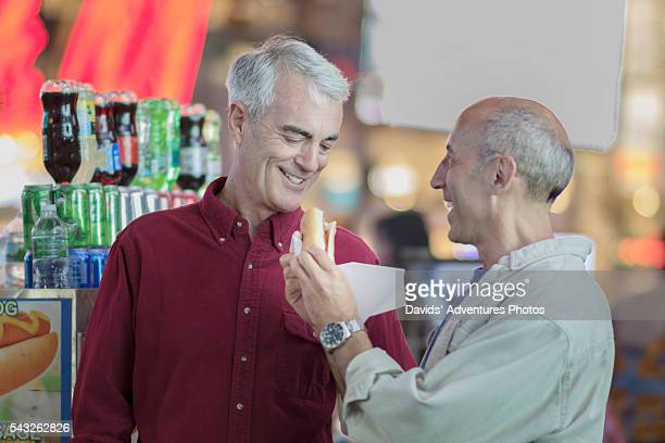 Senior Gay Couple Eating a Hot Dog in New York Times Square