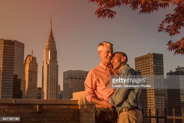 Senior Gay Couple Embracing on Rooftop in New York City at Sunset