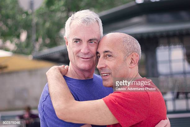 Senior Gay Couple on Vacation Ebracing in Front of Kiosk or Pavilion in City Park