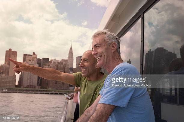 Senior Gay Couple on Vacation on Boat and Pointing into Distance