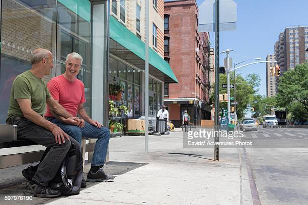 Senior Gay Couple or Two Older Male Friends Talking While They Sit and Wait at City Bus Stop