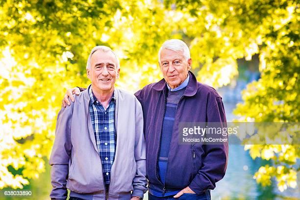 senior gay couple portrait in park at autumn - gay seniors photos et images de collection