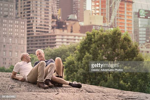 senior gay couple reclining on rocks in new york city central park - gay seniors photos et images de collection