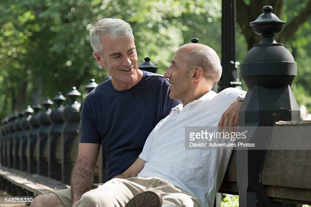 senior gay couple sitting on park bench, smiling and talking - gay seniors photos et images de collection