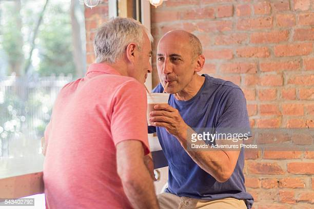 Senior Gay Couple Smiling and Drinking Smoothie or Milkshake from One Cup, Two Straws