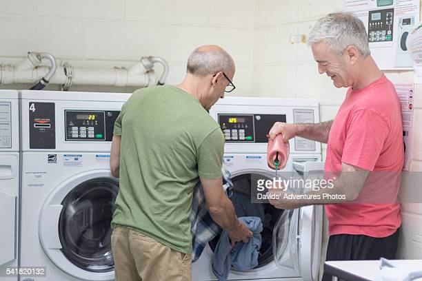 Senior Gay Couple Washing Clothes Together