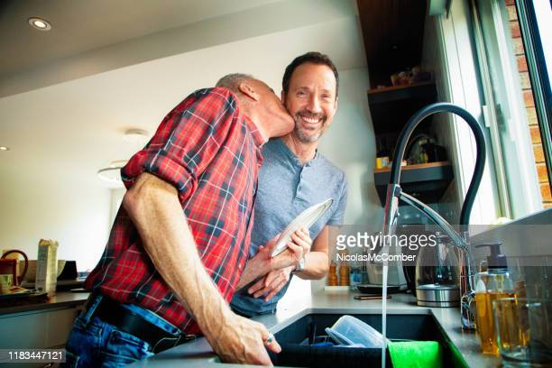 senior gay couple washing dishes together - politics and government stock pictures, royalty-free photos & images