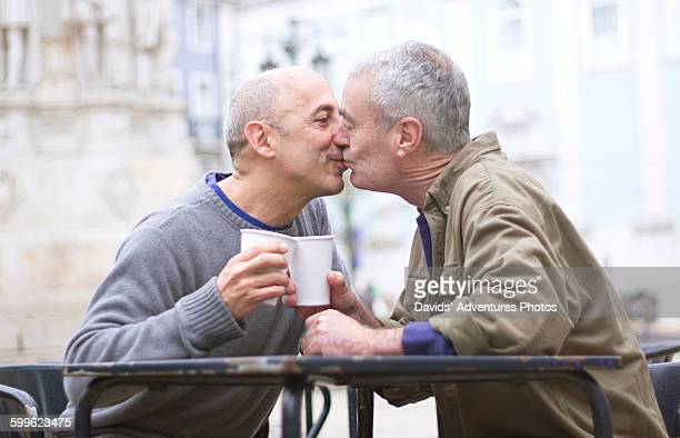 Senior gay male couple having coffee and kissing