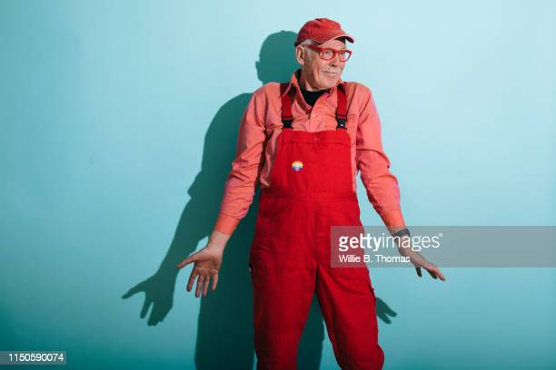 senior gay man in red overalls - coveralls stock pictures, royalty-free photos & images