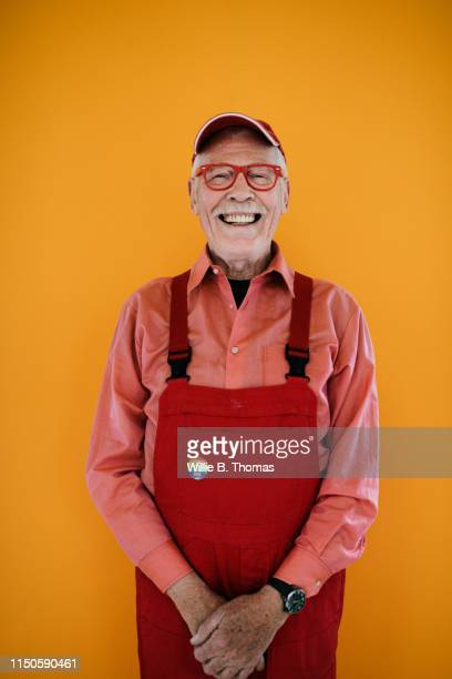 senior gay man in red overalls - orange farbe stock-fotos und bilder