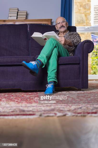 senior gay man reading in his study - one senior man only stock pictures, royalty-free photos & images