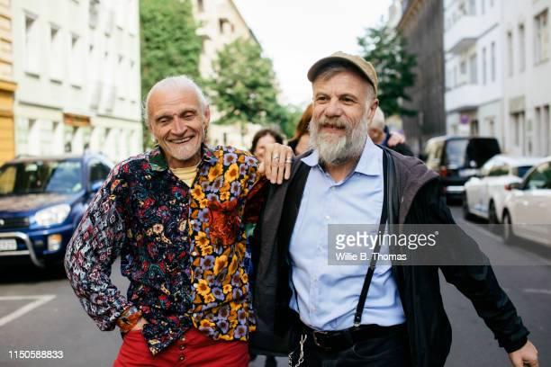 senior gay men walking together - gay seniors photos et images de collection