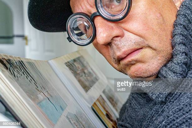 Senior geek wearing thick glasses looking at album