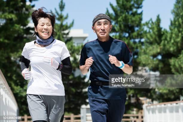 senior generation enjoying jogging with men and women - cheerful ストックフォトと画像