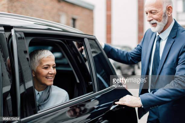 Senior gentleman opening car door for mature business woman