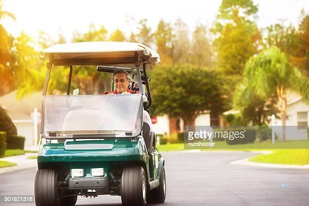 Ältere golfer fahren golf-cart auf golf community road