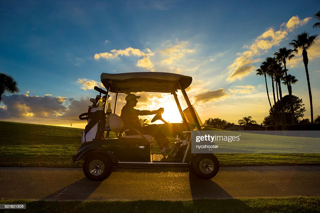 Senior golfer driving golf cart : Stock Photo