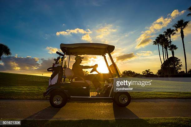 senior golfer driving golf cart - gulf coast states stockfoto's en -beelden