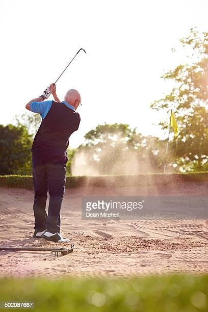 Senior golfer hitting ball out of sand trap