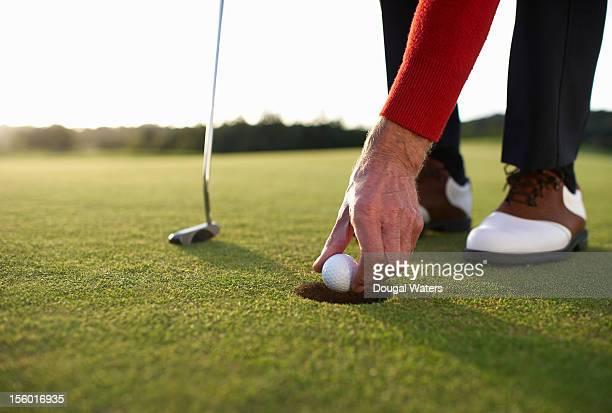 Senior golfer retrieving ball from hole.