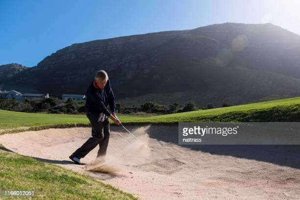 senior golfer taking shot on sand trap in course - chip shot stock pictures, royalty-free photos & images