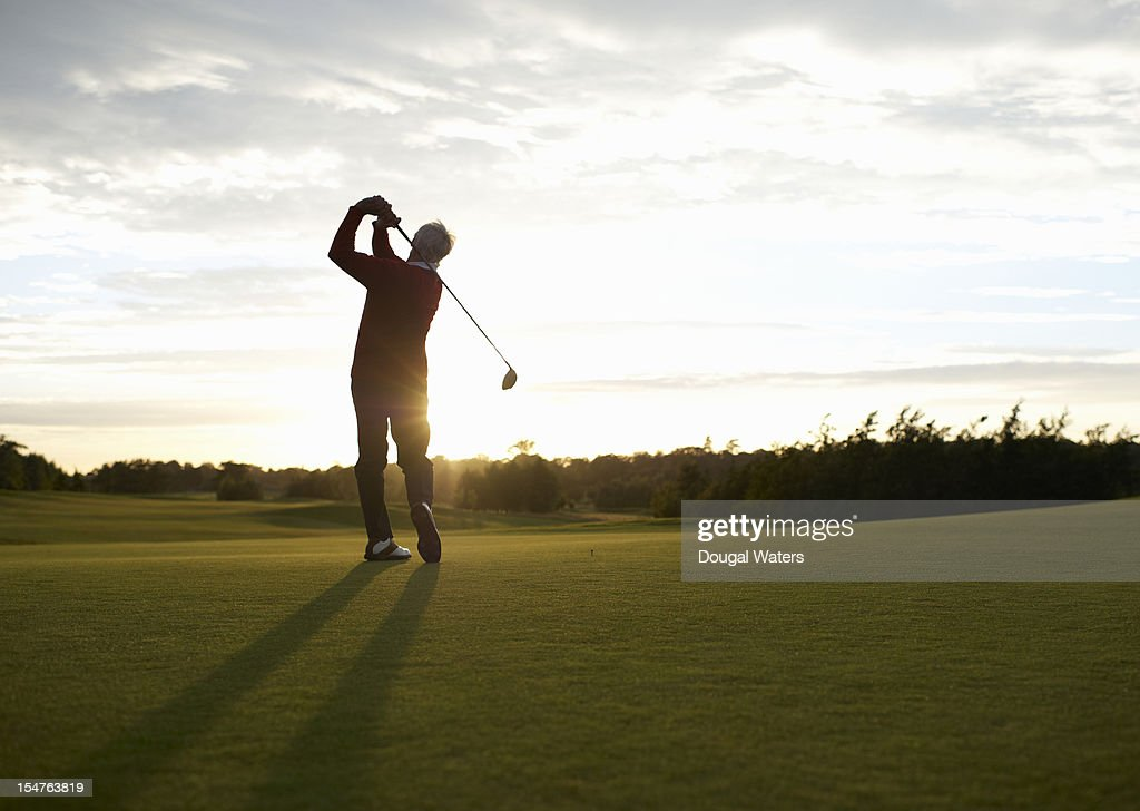 Senior golfer teeing off on golf course. : Stock Photo