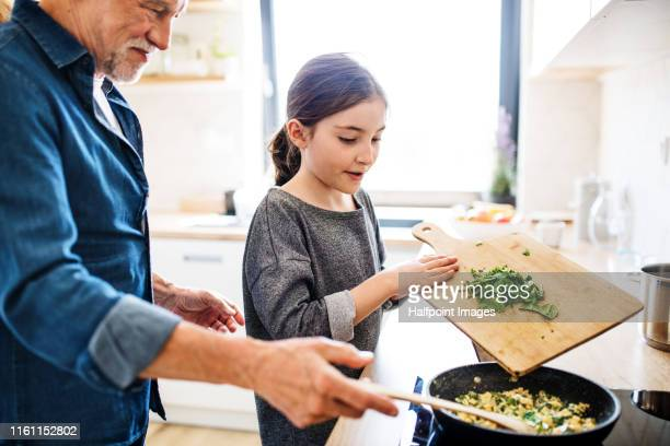 senior grandfather and granddaughter preparing food indoors in kitchen. - koken eten koken stockfoto's en -beelden