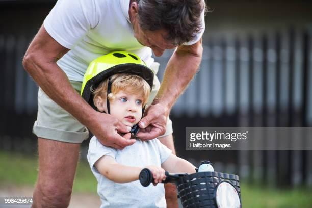 A senior grandfather putting a helmet on a small toddler boys head outdoors. Copy space.