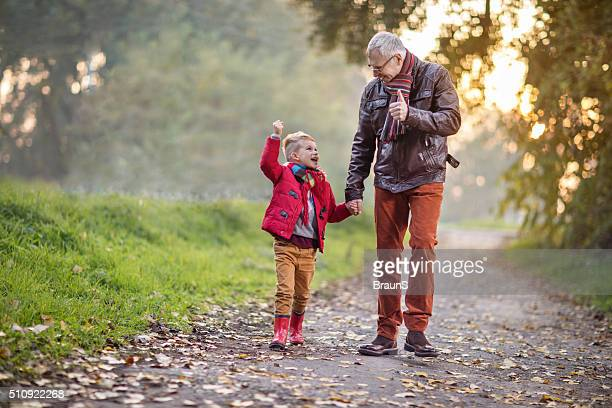 Senior grandfather walking with his grandson and talking to him.