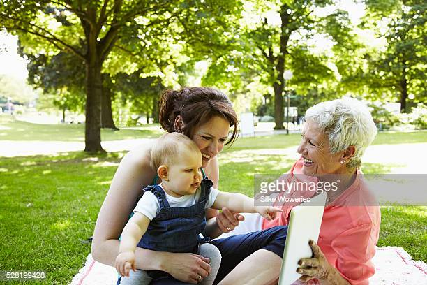 senior grandmother, adult mother and a baby (12- 23 months) enjoying day in park - 12 23 months stock pictures, royalty-free photos & images