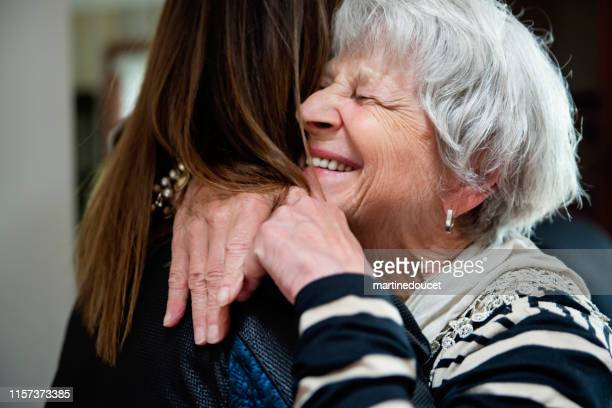 senior grand-mother and adult grand-daughter hugging. - embracing stock pictures, royalty-free photos & images