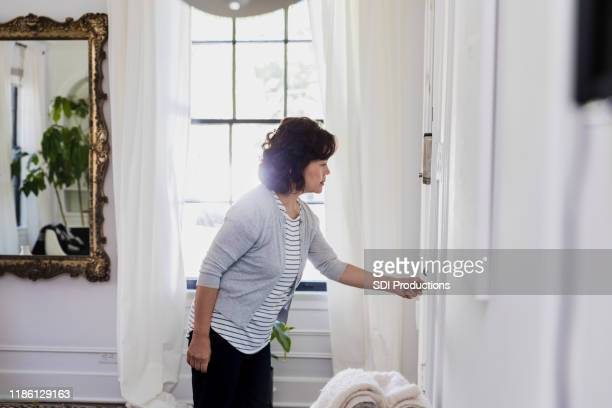 senior grandmother anticipates visit; checks front door - closing stock pictures, royalty-free photos & images