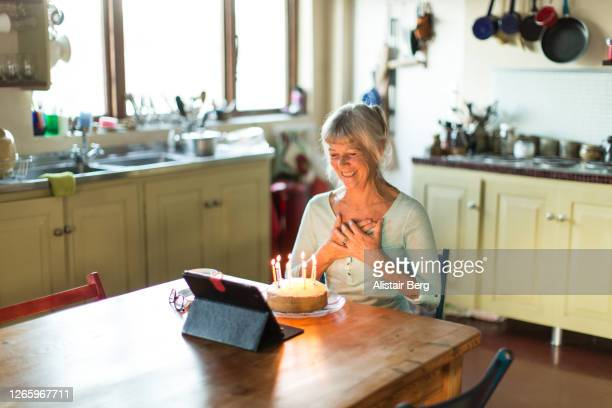 senior grandmother blowing out birthday cake candles on a video call - disruptaging foto e immagini stock