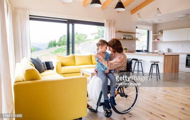 a senior grandmother in wheelchair talking to her small granddaughter indoors at home. - wheelchair stock pictures, royalty-free photos & images
