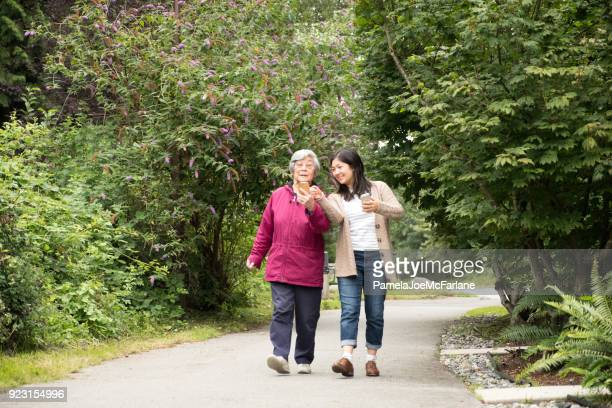 senior grandmother learning to use smartphone while walking with granddaughter - vancouver canada stock pictures, royalty-free photos & images