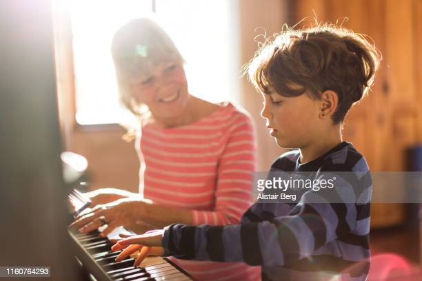 senior grandmother teaching her grandson to play the piano - piano stock pictures, royalty-free photos & images