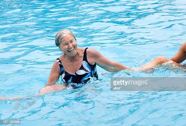 Senior gray hair woman enjoying water aerobics in swimming pool.