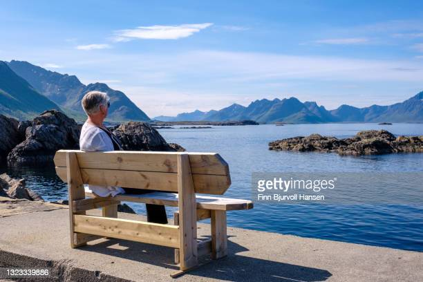 senior grayhaired woman enjoying the ocean view from a bench standing at the pier in nyksund norway - finn bjurvoll stockfoto's en -beelden