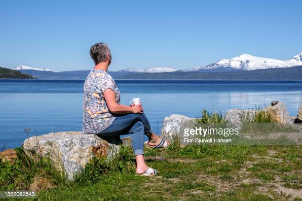 senior grayhaired woman sitting on a stone drinking coffee and looking at the view - finn bjurvoll stock-fotos und bilder