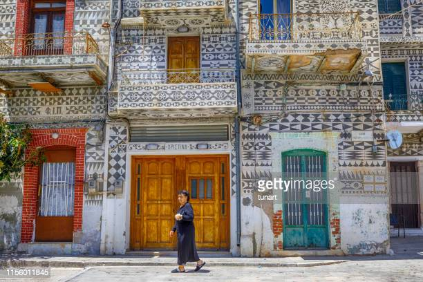 senior greek woman and traditional architecture of pyrgi, chios island, greece - tradition stock pictures, royalty-free photos & images