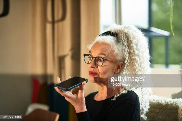 senior grey haired woman talking on speaker phone - working seniors stock pictures, royalty-free photos & images