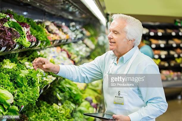 Senior grocery store Mitarbeiter die Verfügbarkeit in Obst und Gemüse-Abschnitt