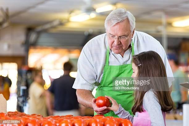 Senior de mercearia dono de loja ajuda a menina em produzir secção