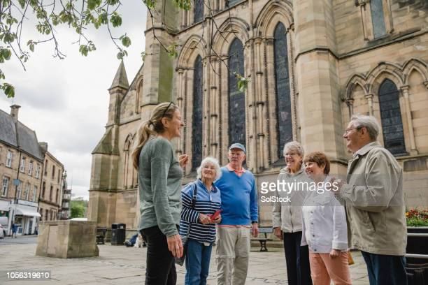 senior group doing a tour in hexham - church stock pictures, royalty-free photos & images