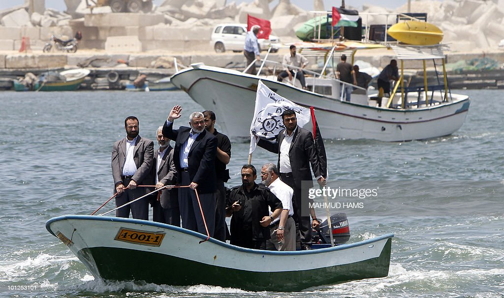 Senior Hamas leader Ismail Haniya (C) waves as he rides a boat off the coast of Gaza City on May 29, 2010 in preparation for the arrival of the 'Freedom Flotilla'. Organisers of the aid flotilla bound for the Gaza Strip in defiance of an Israeli embargo say it is determined to set sail from international waters off Cyprus, despite delays and threats to intercept the ships.