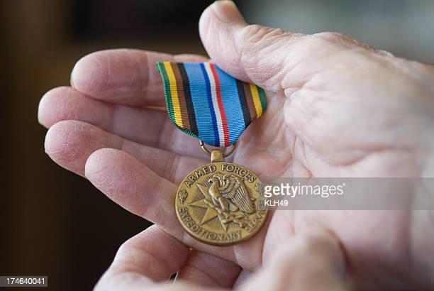Senior hand holding military metal.