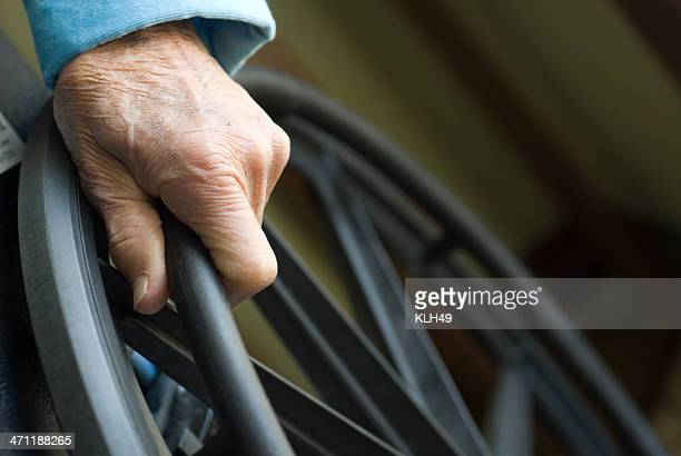 senior hand on wheelchair - social security stock pictures, royalty-free photos & images