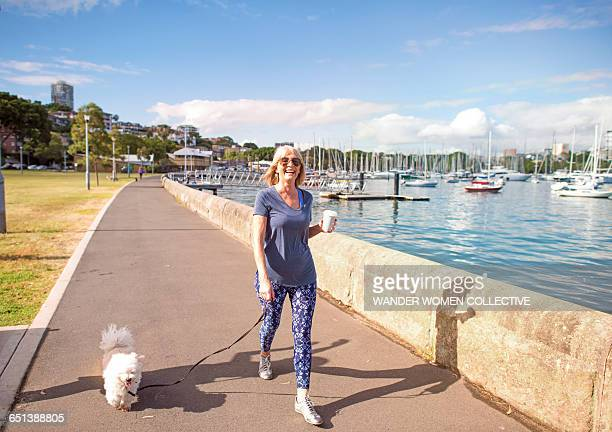 Senior healthy woman with coffee walking dog